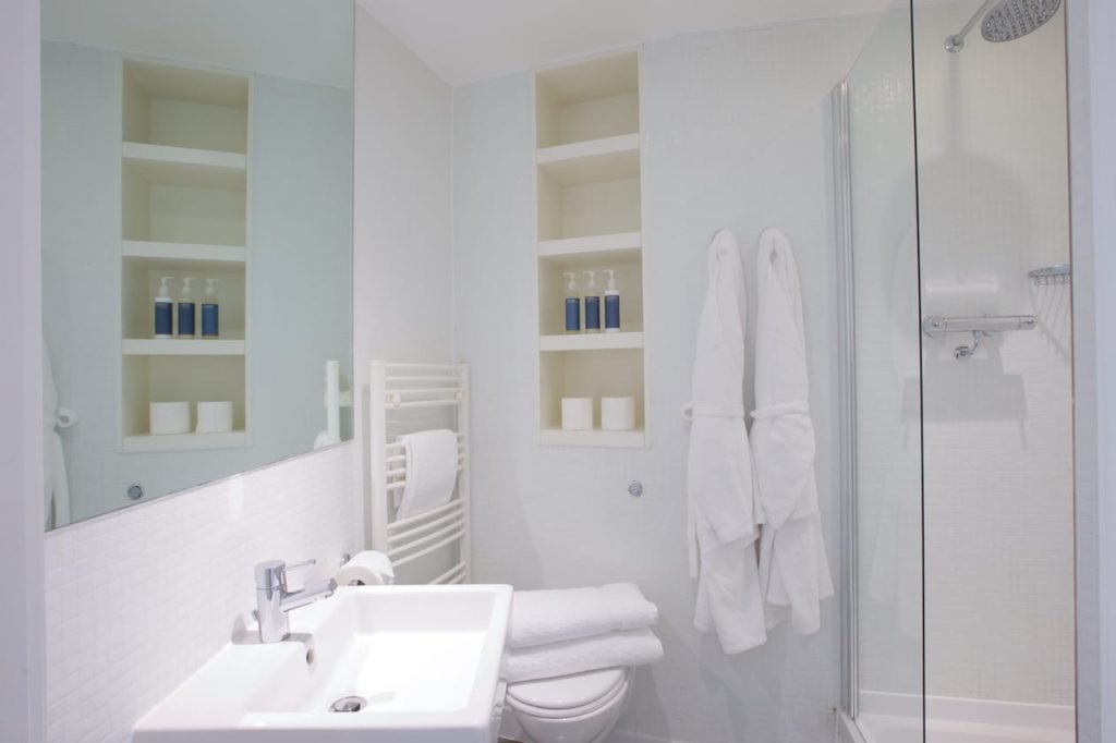 Shower room with bathrobes, towels and toiletries in a studio apartment at Rotunda