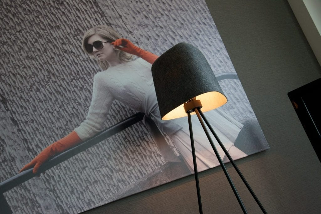 Grey Tom Dixon lamp on tripod in front of large photograph of woman in sunglasses
