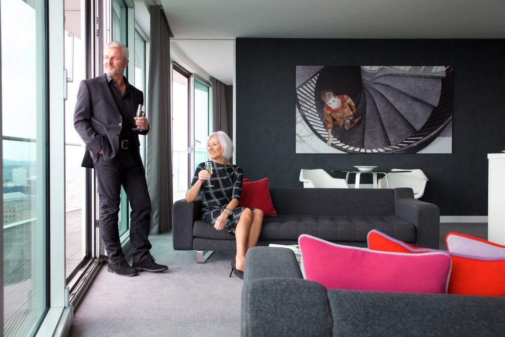 Couple enjoying champagne in a Birmingham penthouse at Staying Cool at the Rotunda