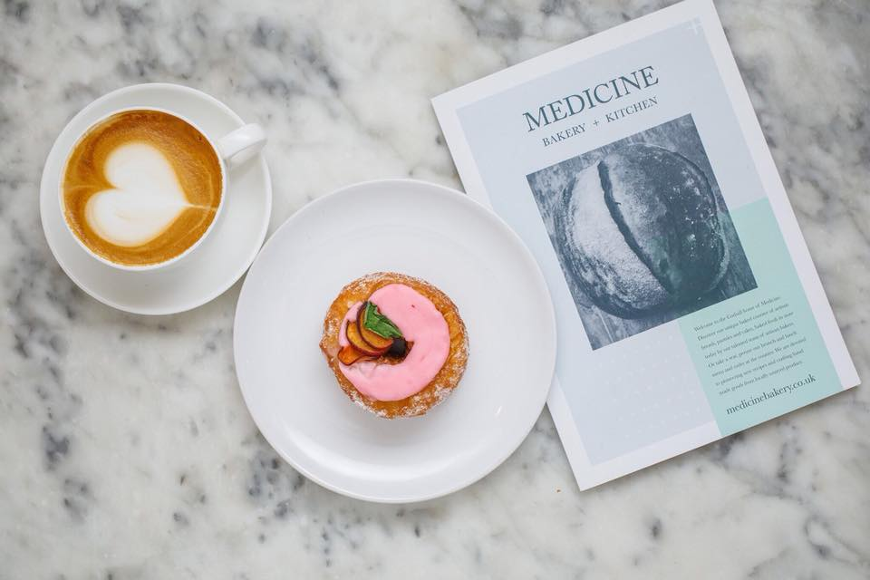 Doughnut and coffee with menu on table at Medicine Bakery, Birmingham