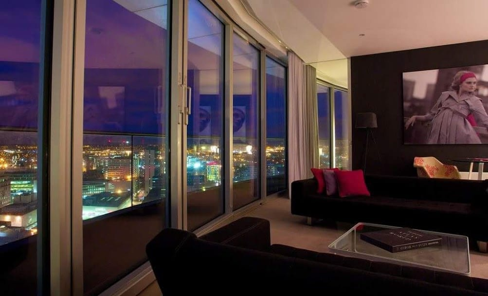 Staying Cool's Rotunda penthouse at night with colourful city views.